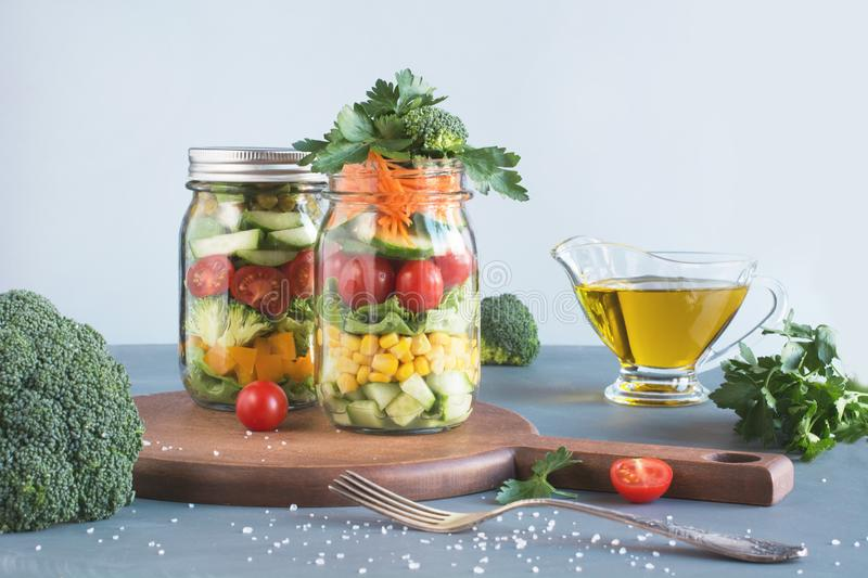 Vegetable healthy homemade colorful salad in mason jar with tomato, lettuce, broccoli on blue. Copy space. Lunch for stock photos