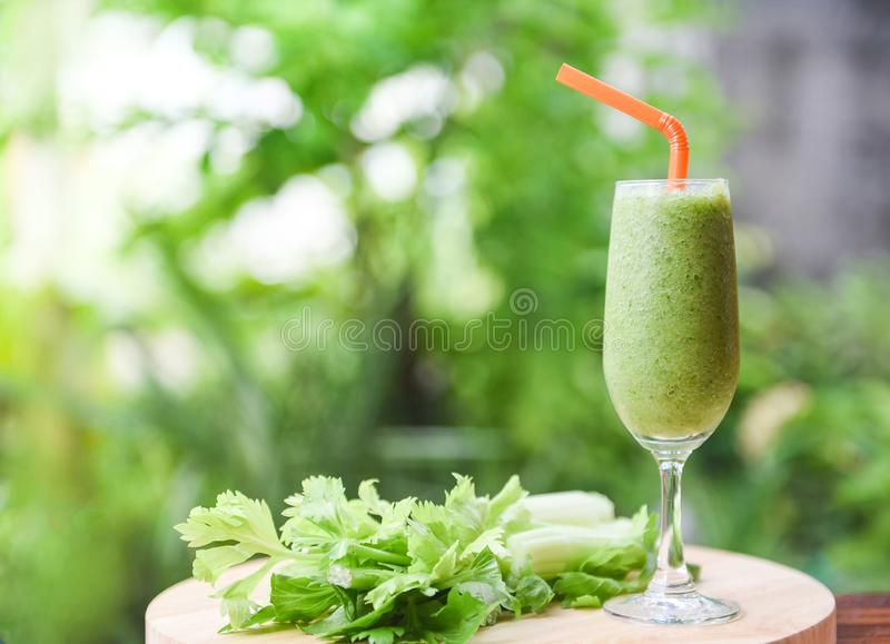 Vegetable juice smoothie summer and fresh celery stalk on wooden board with nature green stock photo