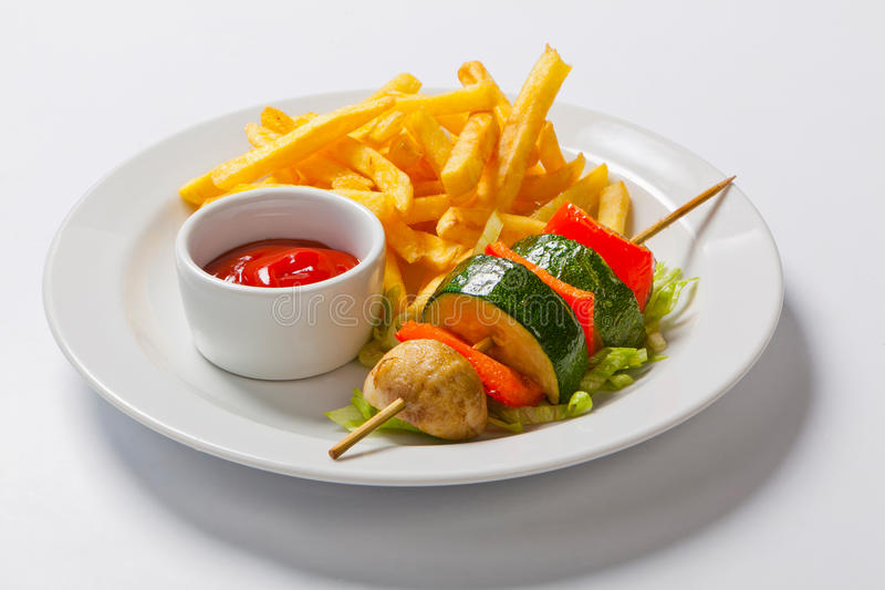 Vegetable kebab. vegetables grilled skewers on plate with french fries stock photo