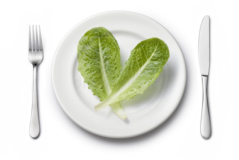 Vegetables Plate Setting Diet. Two romaine lettuce leaves on a white plate setting with a knife and fork stock photo