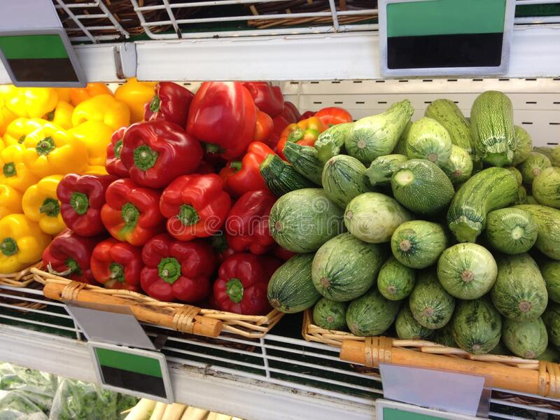 Vegetable marrows and red peppers on a supermarket shelf stock image
