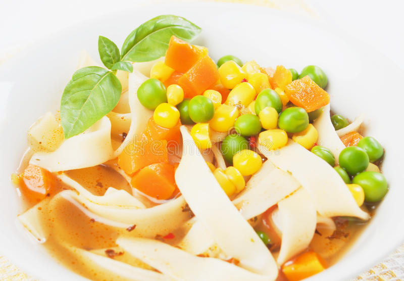 Vegetable noodle soup. With green peas, carrot and corn stock photos