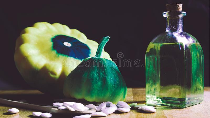 Vegetable oil next to pumpkin seeds on a rustic wooden table against a black cloth background. Empty copy space. For Editor`s text royalty free stock photography