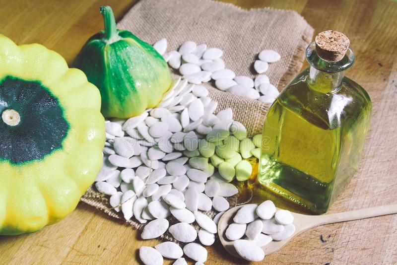 Vegetable oil next to pumpkin seeds on a rustic wooden table in a rural kitchen. Empty copy space. For Editor`s text royalty free stock photography