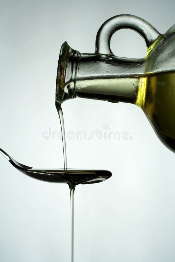 Vegetable Oil On Spoon. Vegetable oil being poured from a carafe onto a spoon. Isolated on white background stock photo