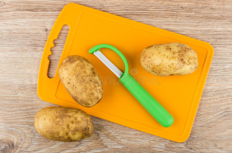 Vegetable peeler with ceramic blade and potatoes on cutting boa stock photo