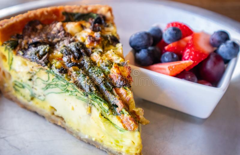Vegetable quiche tart portion served with fresh fruits. Closeup view. French quiche tart with vegetables served with fresh fruits. High angle closeup view royalty free stock photo
