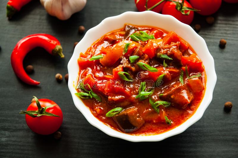 Vegetable rague with eggplant, pepper, tomato and carrot in white bowl on dark wooden background stock photos