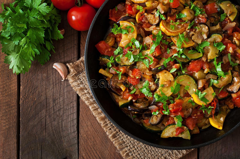 Vegetable Ratatouille in frying pan. On a wooden table stock images