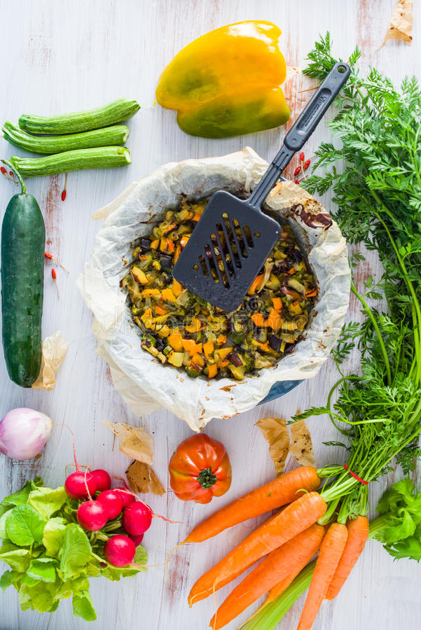 Vegetable ratatouille in a plate. Vegetable ratatouille oven cooked in a plate with cooking paper, over a white rusty table, circled by fresh vegetables royalty free stock photography