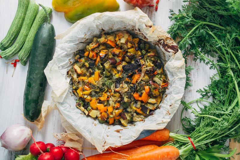 Vegetable ratatouille in a plate. Vegetable ratatouille oven cooked in a plate with cooking paper, over a white rusty table, circled by fresh vegetables royalty free stock image