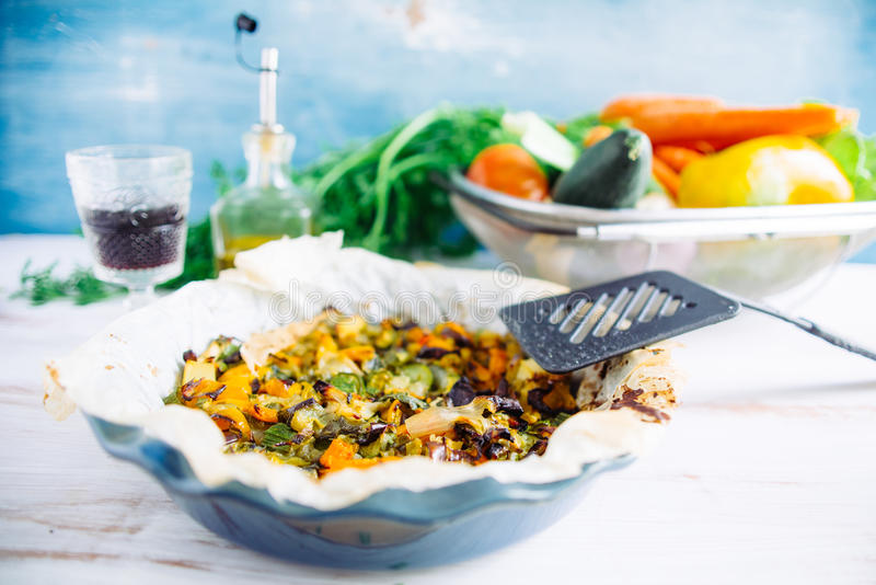 Vegetable ratatouille in a plate. Vegetable ratatouille oven cooked in a plate with cooking paper, over a white rusty table, glass of wine and oil bottle in the stock images