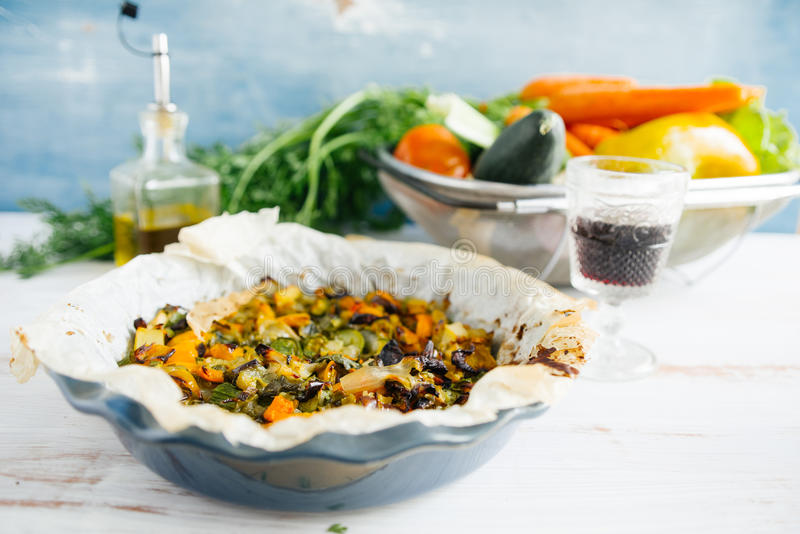 Vegetable ratatouille in a plate. Vegetable ratatouille oven cooked in a plate with cooking paper, over a white rusty table, glass of wine and oil bottle in the royalty free stock images