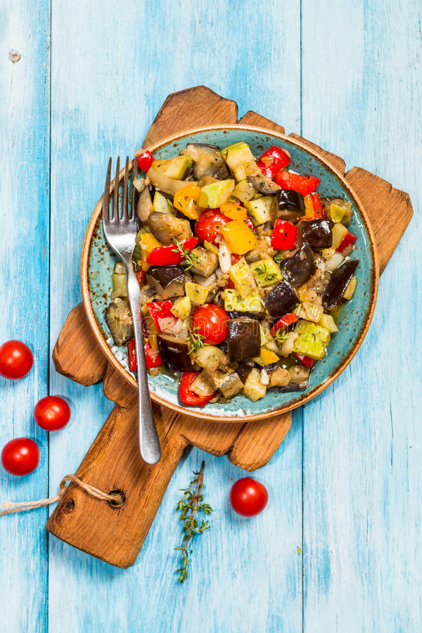 Vegetable ratatouille in a plate. Vegetable ratatouille: steamed zucchini, eggplant, tomatoes, bell peppers, onion, garlic, thyme in a plate on blue background stock image