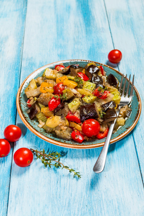 Vegetable ratatouille in a plate. Vegetable ratatouille: steamed zucchini, eggplant, tomatoes, bell peppers, onion, garlic, thyme in a plate on blue background royalty free stock photos