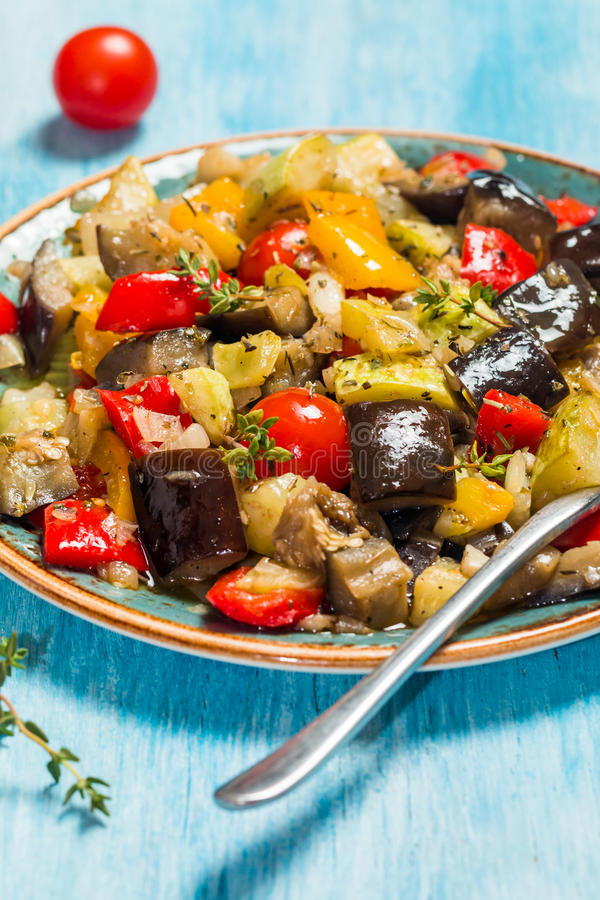 Vegetable ratatouille in a plate. Vegetable ratatouille: steamed zucchini, eggplant, tomatoes, bell peppers, onion, garlic, thyme in a plate on blue background royalty free stock photo