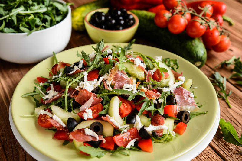 Vegetable salad with Black Forest ham, arugula, cucumber, black olives, red pepper, tomato and Mozzarella royalty free stock photography