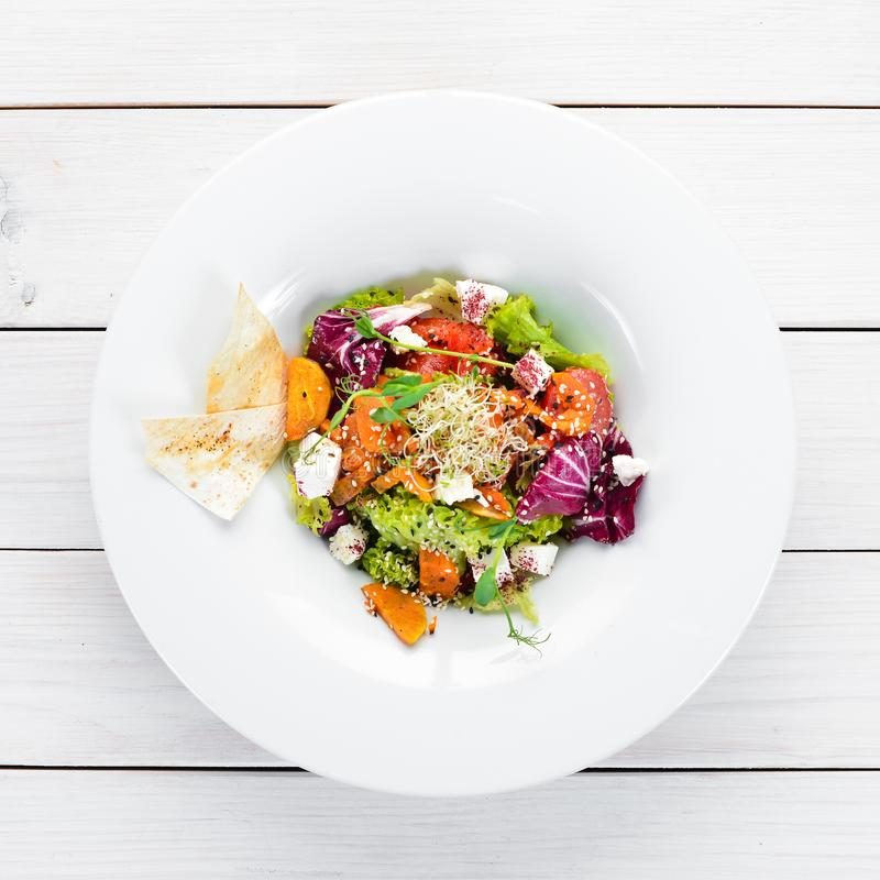 Vegetable salad with cabbage with feta cheese. In the plate. Top view. Free space for your text. Rustic style stock photo