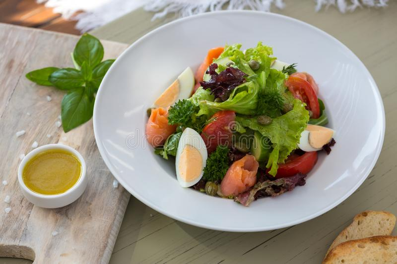 Vegetable salad with egg and salmon served with basil and topping sauce.  royalty free stock photo