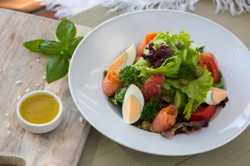 Vegetable salad with egg and salmon served with basil and topping sauce.  royalty free stock images