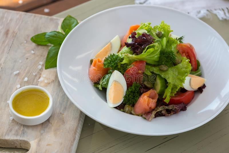 Vegetable salad with egg and salmon served with basil and topping sauce.  royalty free stock photos