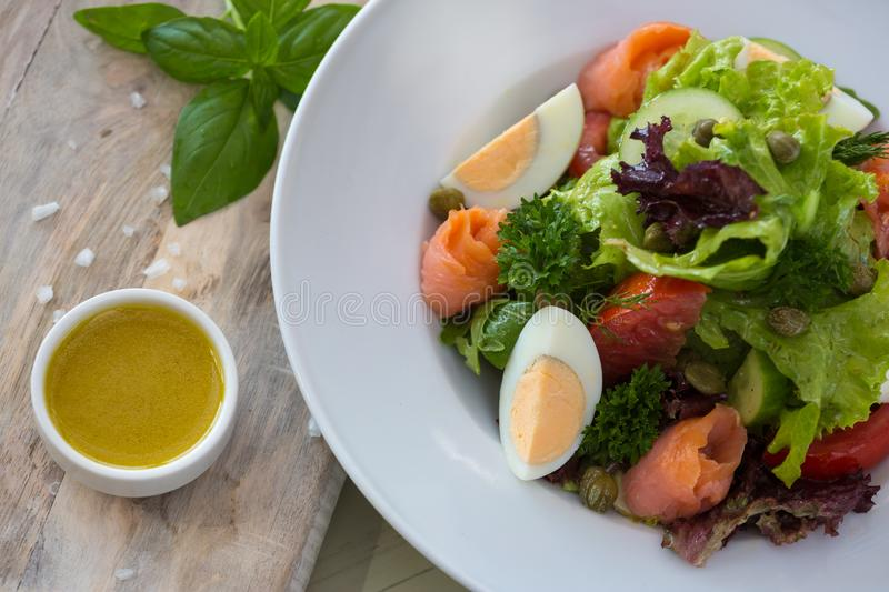 Vegetable salad with egg and salmon served with basil and topping sauce.  stock image