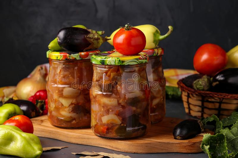 Vegetable salad with eggplant, onions, peppers and tomatoes in jars on a dark background, horizontal orientation. Close up stock photography