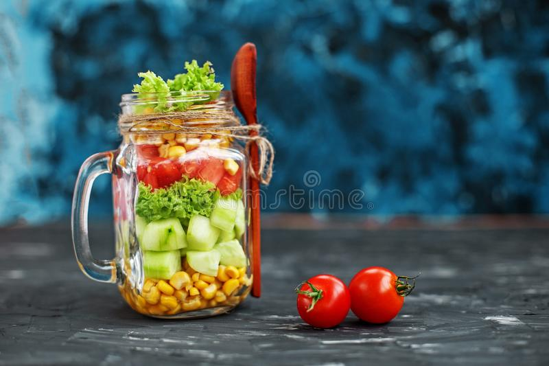 Vegetable salad in a glass jar. Spoon and cherry tomatoes. Healthy food, Diet, Detox, Clean Eating or Vegetarian concept stock image