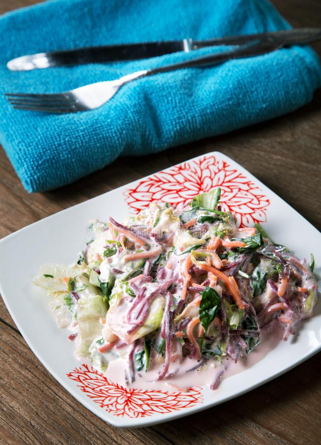 Vegetable salad with mayonnaise dressing and cutlery. On a rustic table stock photography