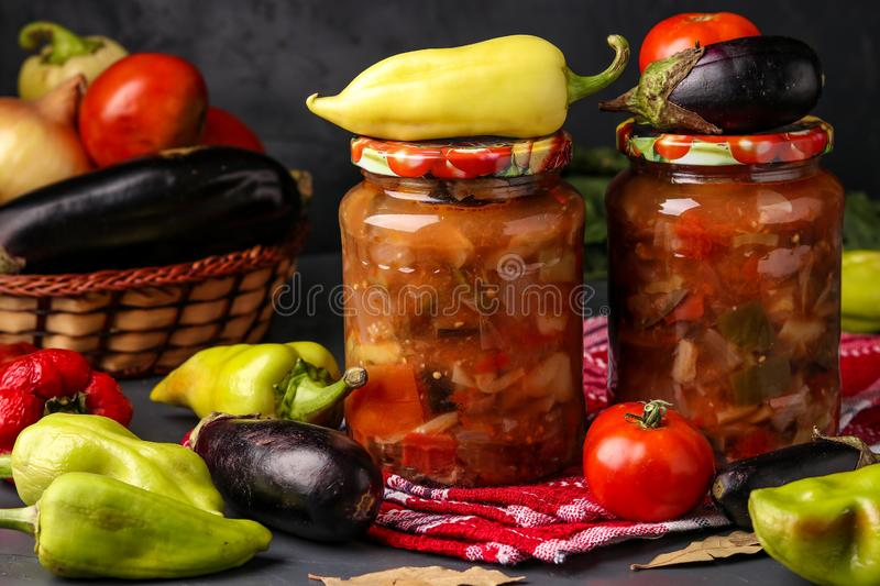 Vegetable salad with peppers, eggplant, onions and tomatoes in jars on a dark background, horizontal orientation. Close up stock image