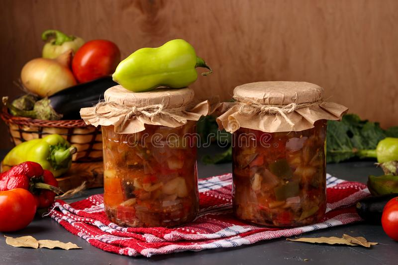 Vegetable salad with peppers, eggplant, onions and tomatoes in jars on a wooden table, horizontal orientation. Close up stock photos