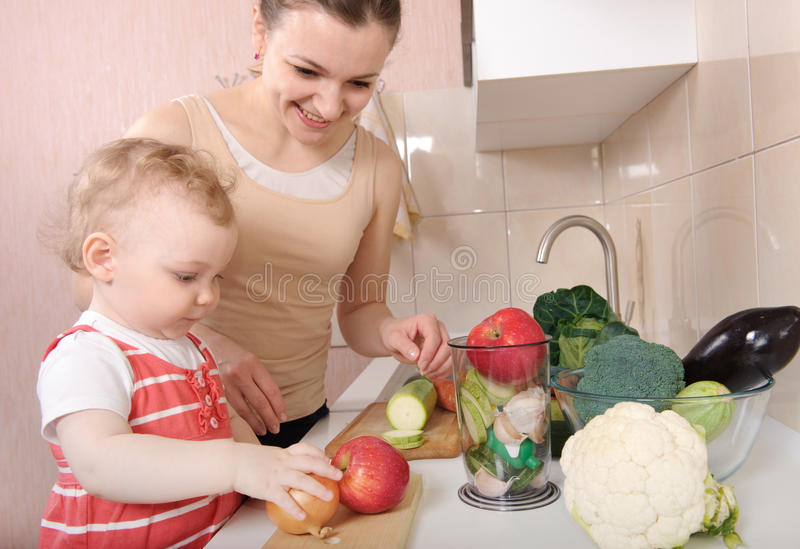 Vegetable salad preparation. Young mother preparing fresh vegetable salad with her baby daughter royalty free stock image