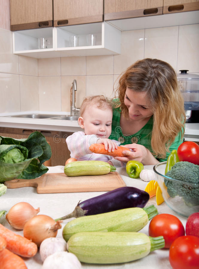 Vegetable salad preparation. Young mother preparing fresh vegetable salad with her baby daughter stock photo
