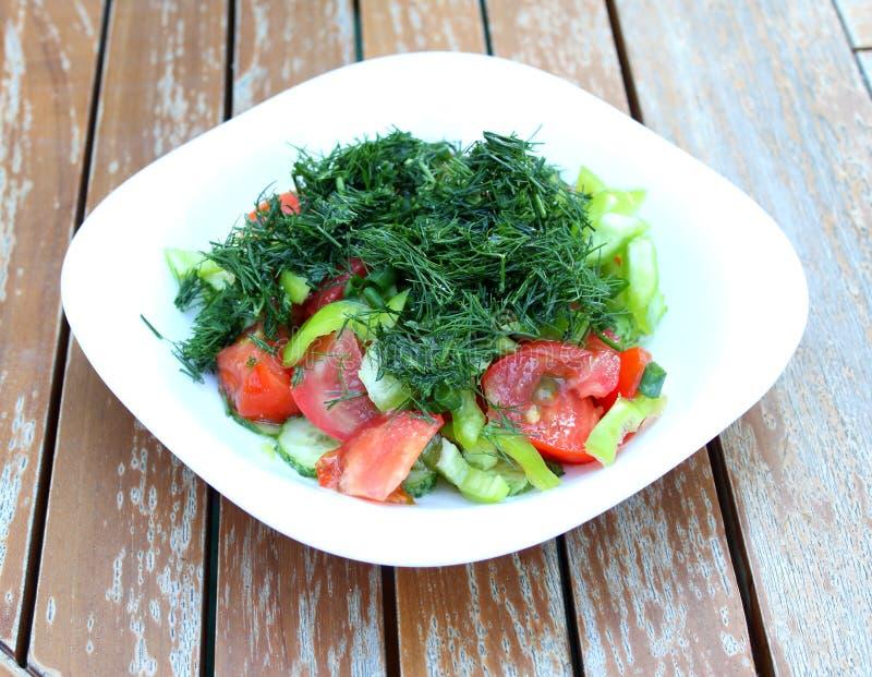 Vegetable salad in white plate on garden table.
