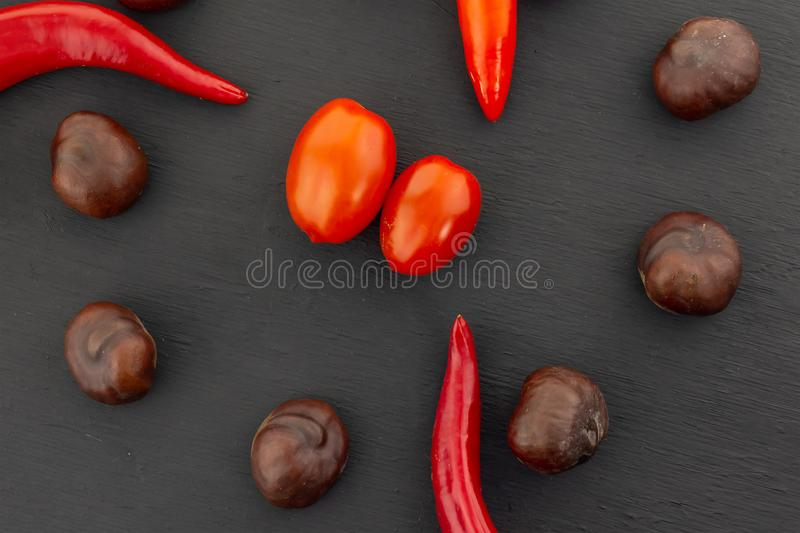 Vegetable set red tomato mini in the center of a brown chestnut brown chili pepper on a black background close-up stock images