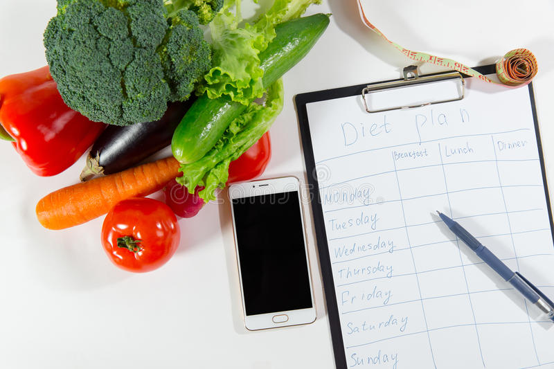 Vegetable for slimming, mobile phone and diet plan stock photos