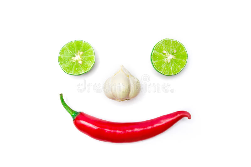 Vegetable smiling face from red chili pepper , garlic and lime on white background royalty free stock photo