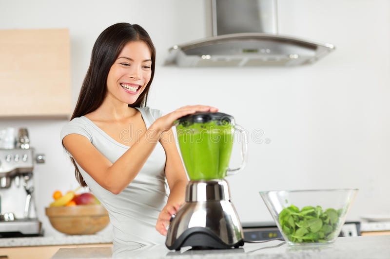 Vegetable smoothie woman blending green smoothies. With blender home in kitchen. Healthy eating lifestyle concept portrait of beautiful young woman preparing stock images