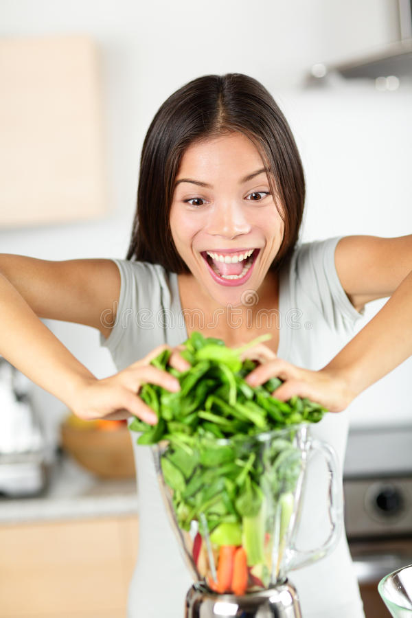 Vegetable smoothie woman making green smoothies. With blender home in kitchen. Funny healthy raw eating lifestyle concept portrait of beautiful young woman stock image