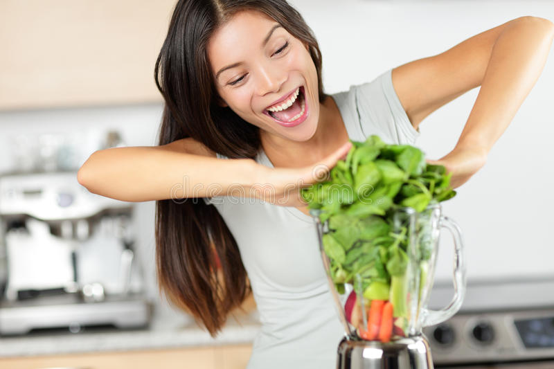 Vegetable smoothie woman making green smoothies. With blender home in kitchen. Healthy raw eating lifestyle concept portrait of beautiful young woman preparing royalty free stock photos