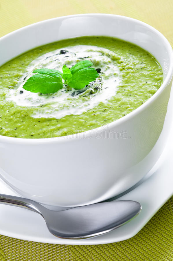 Vegetable soup. Fresh vegetable soup topped with cream and mint royalty free stock photography