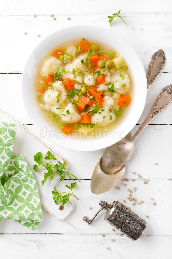 Vegetable soup with cauliflower, carrot, green peas, onion and potato stock photos