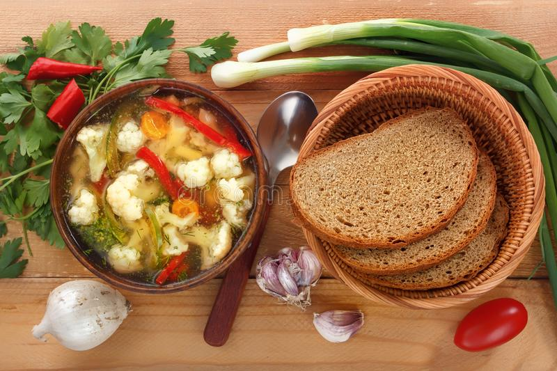 Vegetable soup of cauliflower, carrots, tomato, pepper in a plate with a spoon, bread and onions on a wooden background. Close-up. Top view royalty free stock photography