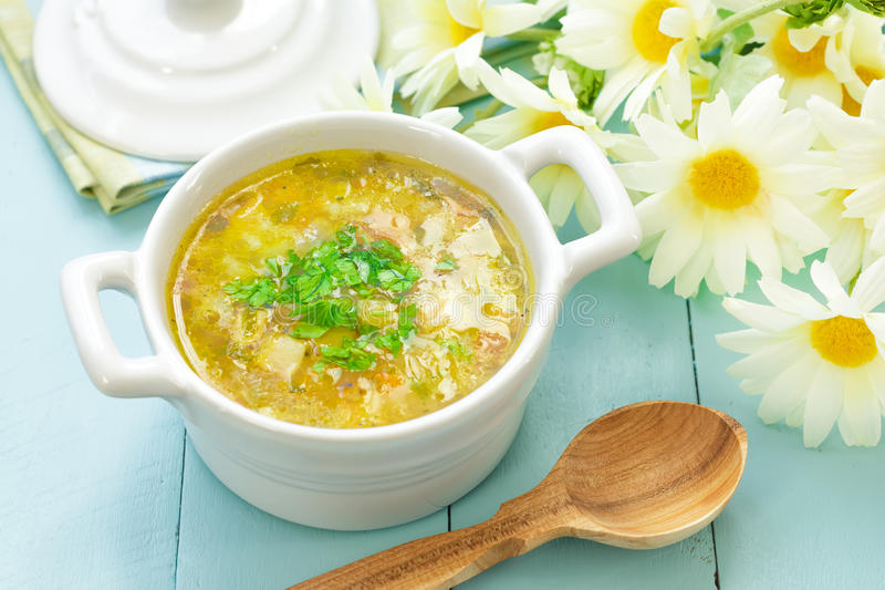 Vegetable soup. Fresh vegetable soup in a rustic bowl with a wooden spoon stock photos