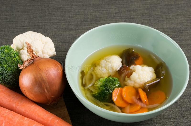 Vegetable soup with onion, carrot, cauliflower, broccoli and seaweed in green dish on brown tablecloth, and fresh vegetable next t stock images