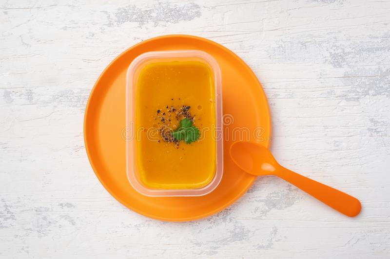 Vegetable soup on an orange plastic plate. A portion of vegetable lentil soup in a plastic container on an orange plastic plate standing on a white wooden table stock images