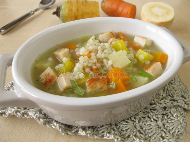 Vegetable soup with pearl barley and chicken. In bowl royalty free stock photos