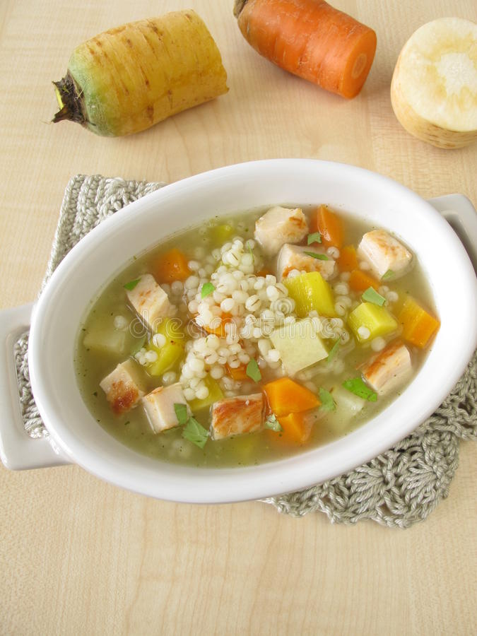 Vegetable soup with pearl barley and chicken. In bowl royalty free stock photo