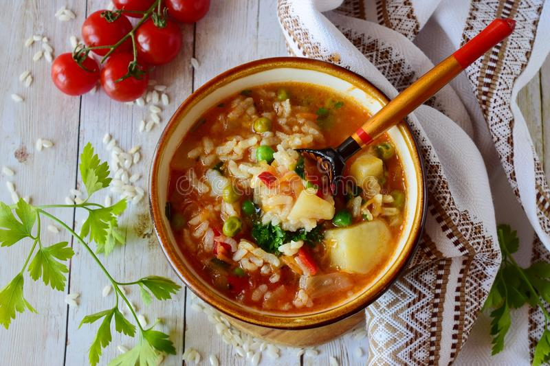 Vegetable soup with rice. Tomato, potato, green peas, carrots and onions. Healthy eating concept royalty free stock photo