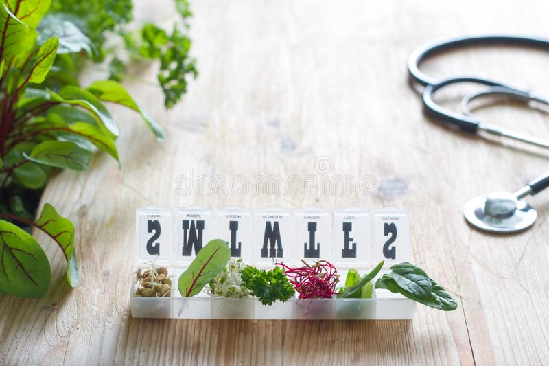 Vegetable sprouts and herbs in the box healthy life style and alternative medicine concept. On wooden background royalty free stock photography
